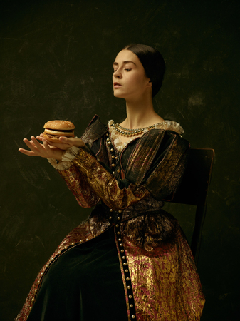 Portrait of a girl wearing a princess or countess dress over dark studio. portrait with burger Фото со стока