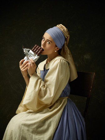 Medieval woman in historical costume wearing corset dress and bonnet. Beautiful peasant girl wearing thrush costume with sweet chocolate bar over dark studio Imagens