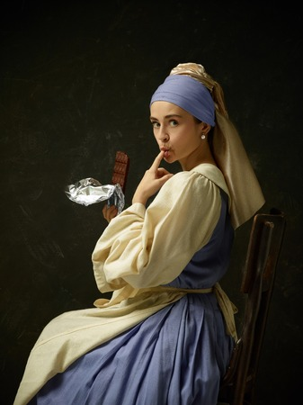 Medieval woman in historical costume wearing corset dress and bonnet. Beautiful peasant girl wearing thrush costume with sweet chocolate bar over dark studio 写真素材