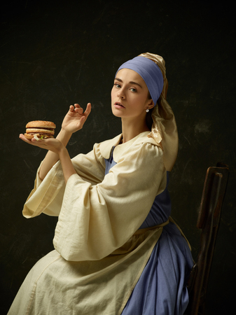 Medieval Woman in Historical Costume Wearing Corset Dress and Bonnet with burger. Beautiful peasant girl wearing thrush costume