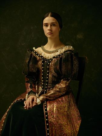 Porträt eines Mädchens, das ein Prinzessinnen- oder Gräfinkleid über einem dunklen Studio trägt Standard-Bild