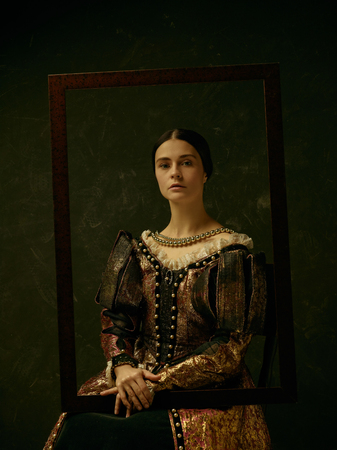 Portrait of a girl wearing a princess or countess dress over dark studio. portrait through picture frame