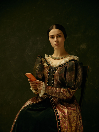 Portrait of a girl wearing a princess or countess dress with mobile phone over dark studio Stock fotó