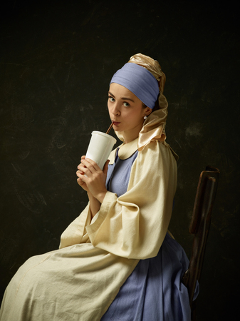 Medieval Woman in Historical Costume Wearing Corset Dress and Bonnet. Beautiful peasant girl wearing thrush costume with  Cola