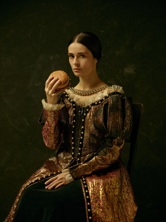 Portrait of a girl wearing a princess or countess dress over dark studio. portrait with burger Stockfoto