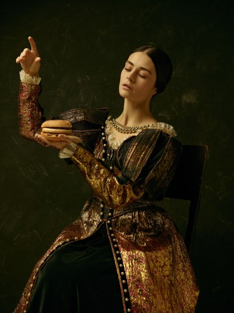 Portrait of a girl wearing a princess or countess dress over dark studio. portrait with burger Stock fotó