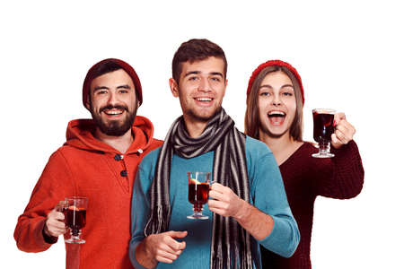 Smiling european men and women during party photoshoot. The guys posing as friends at studio fest with wineglasses with hot mulled wine on foreground. Stok Fotoğraf