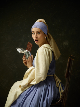 Mujer medieval en traje histórico vistiendo corsé y capot. Hermosa campesina vestida con traje de candidiasis oral con barra de chocolate dulce sobre estudio oscuro