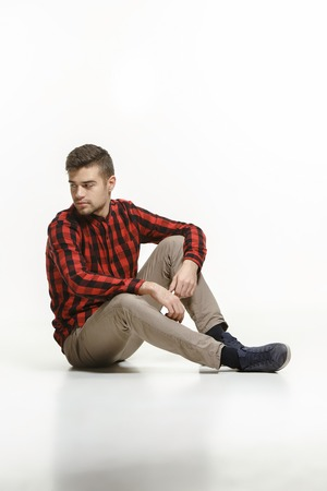Casual young man sitting on the floor and looking to a side, away from the camera, on a white studio background
