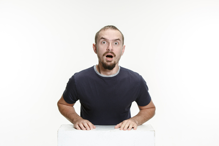 Wow. Attractive male half-length front portrait on studio backgroud. Young emotional surprised bearded man with open mouth. Human emotions, facial expression concept