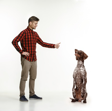 Emotional Portrait of man and his dog, concept of friendship and care of man and animal. German Shorthaired Pointer - Kurzhaar puppy dog isolated on white studio background Reklamní fotografie