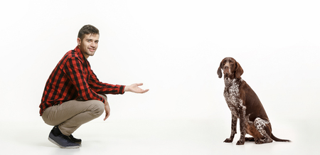 Emotional Portrait of man and his dog, concept of friendship and care of man and animal. German Shorthaired Pointer - Kurzhaar puppy dog isolated on white studio background Stock Photo