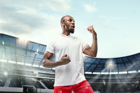 The football african player in motion on the field of stadium at day. The professional football, soccer player and human emotions concept. The win, winner, victory concept Stock Photo