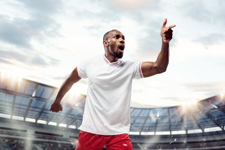 The football african player in motion on the field of stadium at day. The professional football, soccer player and human emotions concept. The win, winner, victory concept Фото со стока