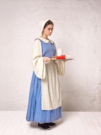 Mujer medieval en traje histórico con vestido corsé y capot. Hermosa niña campesina con traje de candidiasis bucal Foto de archivo