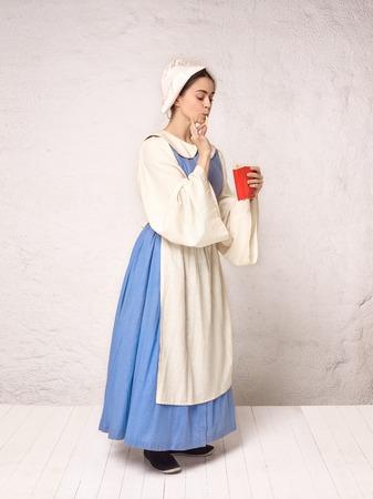 Mujer medieval en traje histórico con vestido corsé y capot. Hermosa campesina vestida con traje de candidiasis oral con papas fritas