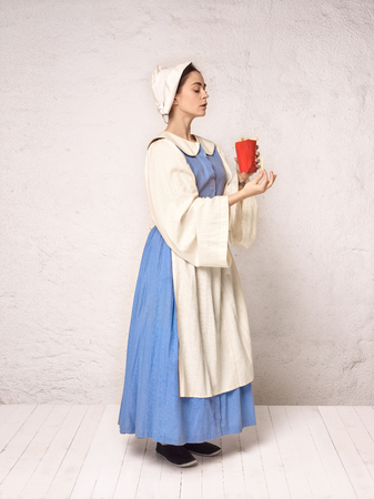 Medieval Woman in Historical Costume Wearing Corset Dress and Bonnet. Beautiful peasant girl wearing thrush costume with French fries Stock Photo