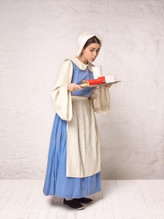 Femme médiévale en costume historique portant une robe corset et un bonnet. Belle paysanne en costume de muguet