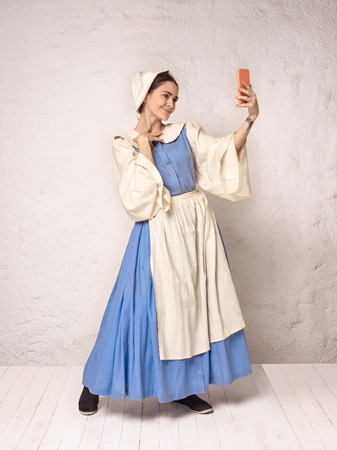 Medieval Woman in Historical Costume Wearing Corset Dress and Bonnet. Beautiful peasant girl wearing thrush costume with mobile phone