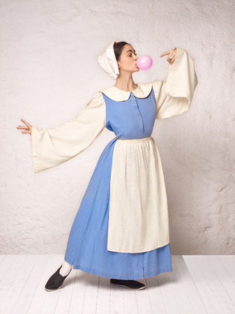 Medieval Woman in Historical Costume Wearing Corset Dress and Bonnet. Beautiful peasant girl wearing thrush costume with bubble gum