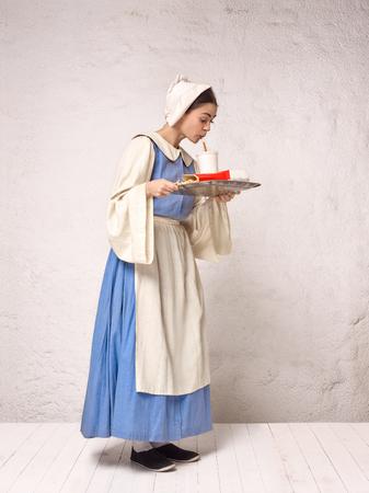 Donna medievale in costume storico che indossa abito corsetto e cofano. Bella contadina che indossa un costume da tordo