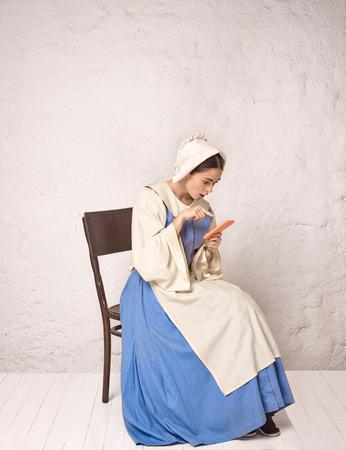 Femme médiévale en costume historique portant une robe corset et un bonnet. Belle paysanne en costume de muguet avec téléphone portable Banque d'images