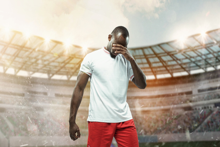 The football african player in motion on the field of stadium at day. The professional football, soccer player and human emotions concept. The dispute with the fate, claim, failure, defeat concept