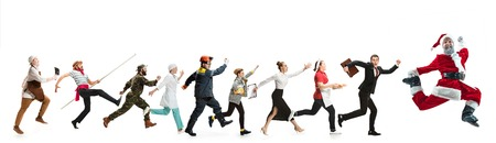Collage of different professions. Group of men, women in uniform running at studio with Santa isolated on white. Full length of people with different occupations. Christmas and holiday concept