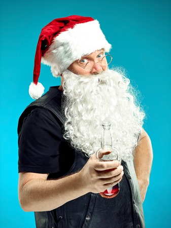 Portrait of Man in Santa Claus Costume - with a Luxurious White Beard, Santas Hat and a Red Costume at red studio background with beer