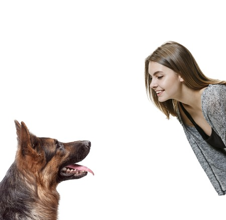 The smiling happy woman and her dog over white background. Shetland Sheepdog sitting in front of a white studio background. The concept of humans and animals same emotions
