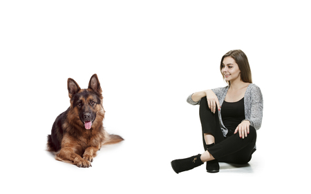 The smiling woman and her dog over white background. Shetland Sheepdog sitting in front of a white studio background. The concept of humans and animals same emotions Stock Photo - 111692014