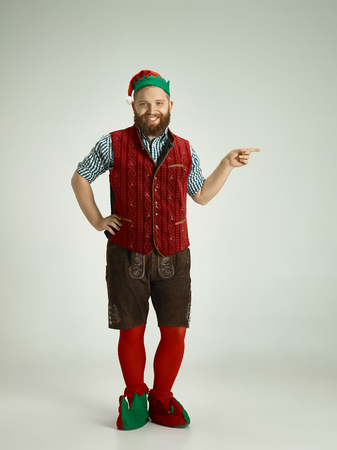 The happy smiling friendly man dressed like a funny gnome or elf pointing to left on an isolated gray studio background. The winter, holiday, christmas concept