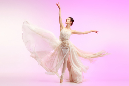 Young graceful female ballet dancer or classic ballerina dancing at pink studio. Caucasian model on pointe shoes Stok Fotoğraf - 111691249