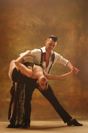 Flexible young modern couple dancing tango in studio. Fashion portrait of attractive dancing couple. Man and woman. Passion. Love. perfect skin facial and make-up. Human emotions - love and passion Фото со стока