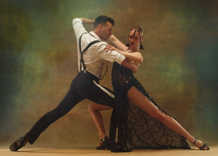 Flexible young modern couple dancing tango in studio. Fashion portrait of attractive dancing couple. Man and woman. Passion. Love. perfect skin facial and make-up. Human emotions - love and passion Stock fotó