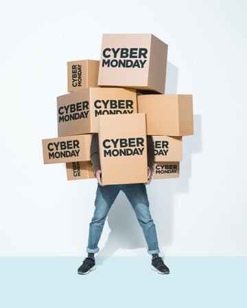 The lot of gift boxes in the hands of young man on white studio background. Cyber monday, shopping, holiday, happy Christmas, sales season start concept