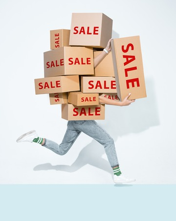 The lot of gift boxes in the hands of young man on white studio background. Cyber monday, shopping, black friday, sale, holiday, happy Christmas, sales season start concept
