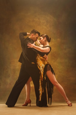 The young dance ballroom couple in gold dress dancing in sensual pose on studio background. Professional dancers dancing tango. Ballroom dance concept. Human emotions - love and passion Stock Photo