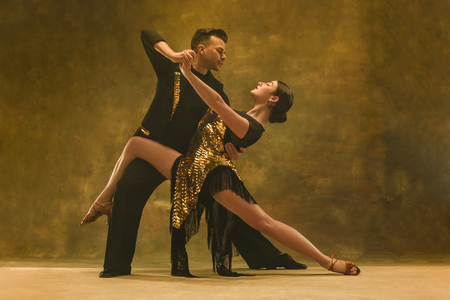 The young dance ballroom couple in gold dress dancing in sensual pose on studio background. Professional dancers dancing tango. Ballroom dance concept. Human emotions - love and passion Banque d'images