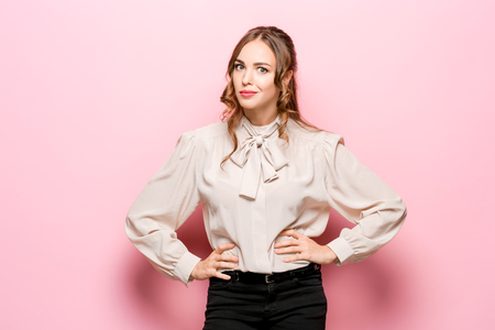 What is it. The female portrait isolated on pink studio backgroud. Anger. Young, emotional, angry, scared woman looking at camera. Human emotions, facial expression concept. Stock Photo