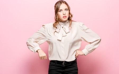What is it. The female portrait isolated on pink studio backgroud. Anger. Young, emotional, angry, scared woman looking at camera. Human emotions, facial expression concept. Stock fotó