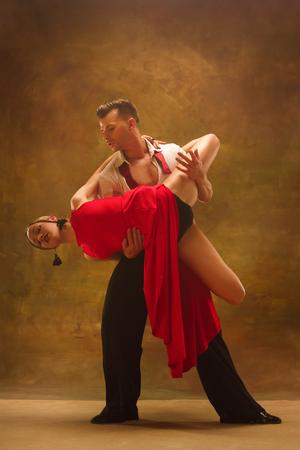 Flexible junge moderne Paare tanzen Tango im Studio. Modeporträt von attraktiven Tanzpaaren. Mann und Frau. Leidenschaft. Liebe. perfektes Haut-Gesicht und Make-up. Menschliche Emotionen - Liebe und Leidenschaft Standard-Bild