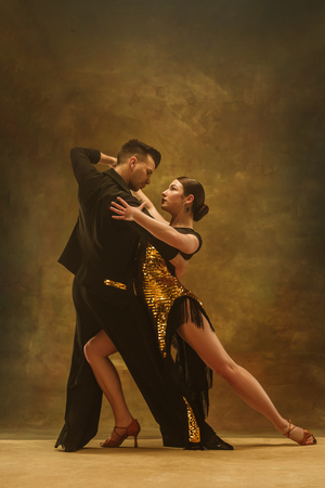 The young dance ballroom couple in gold dress dancing in sensual pose on studio background. Professional dancers dancing tango. Ballroom dance concept. Human emotions - love and passion Stockfoto