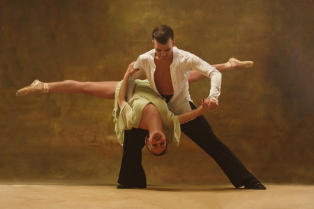 Flexible young modern couple dancing tango in studio. Fashion portrait of attractive dancing couple. Man and woman. Passion. Love. perfect skin facial and make-up. Human emotions - love and passion Stock Photo