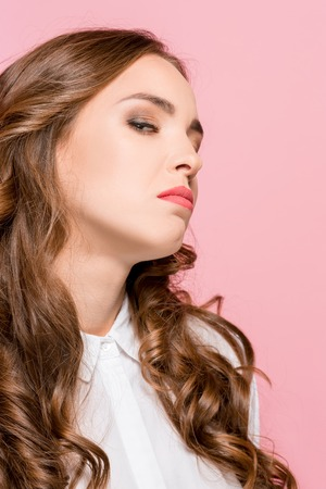 Portrait of young woman arrogantly looking in camera isolated on pink studio background Stock Photo