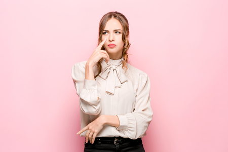 Remember all. Let me think. Doubt concept. Doubtful, thoughtful woman remembering something. Young emotional woman. Human emotions, facial expression concept. Studio. Isolated on trendy pink Foto de archivo