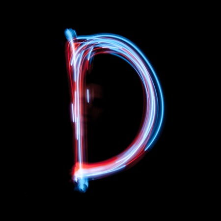 Letter D of the alphabet made from neon sign. The blue light image, long exposure with colored fairy lights, against a black background
