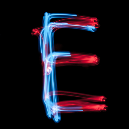 Letter E of the alphabet made from neon sign. The blue light image, long exposure with colored fairy lights, against a black background