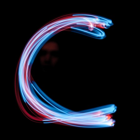 Letter Ð¡ of the alphabet made from neon sign. The blue light image, long exposure with colored fairy lights, against a black background