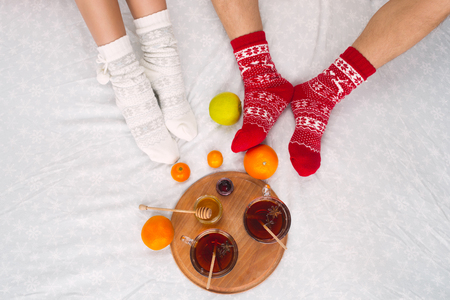 Soft photo of woman and man on the bed with cup of tea and fruits, top view point. Female and male legs of couple in warm woolen socks. Christmas, love, lifestyle concept Stock Photo